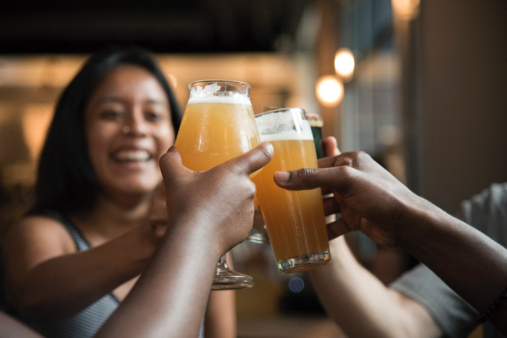 Woman drinking beer with friends.